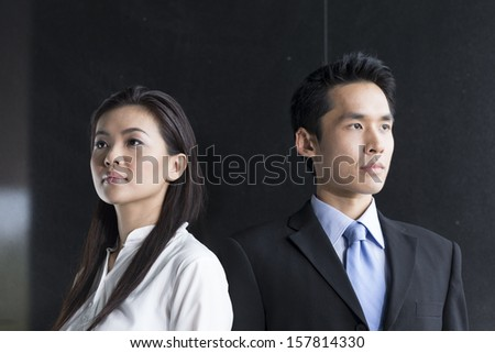 Portrait of two serious Chinese business people standing in front of a black wall. - stock photo