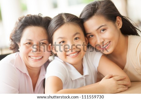Portrait of two sisters and mother smiling at camera - stock photo