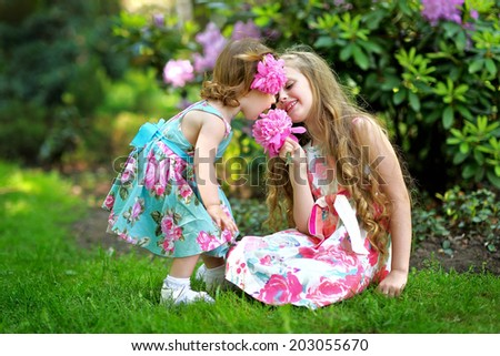 portrait of two sisters in a park in spring - stock photo