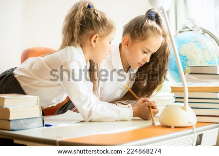Portrait of two sisters in uniform doing homework - stock photo