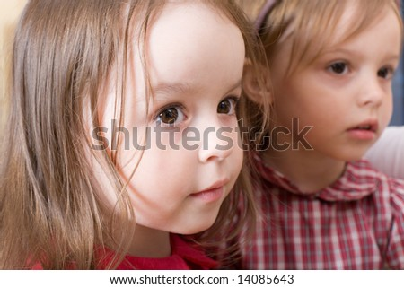 Portrait of two sisters with interest looking at mother