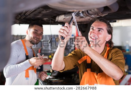 Portrait of two smiling car mechanics at workshop - stock photo