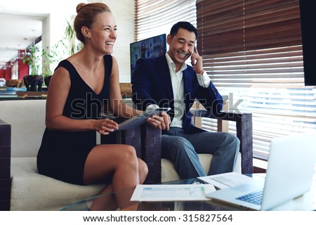 Portrait of two smiling cheerful entrepreneurs preparing for meeting, young woman using touch pad, intelligent men having mobile phone conversation, smart employers busy working in modern office space - stock photo