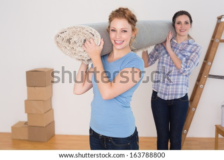 Portrait of two smiling female friends carrying rolled rug after moving in a house - stock photo