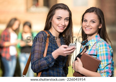 Portrait of two smiling, female students at the college, outdoors. The students in the background. - stock photo