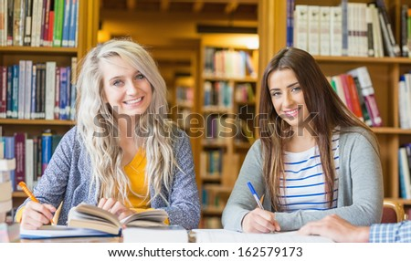 Portrait of two smiling female students writing notes at desk in the college library