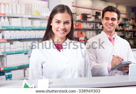 Portrait of two smiling pharmacists in uniform working in modern pharmacy