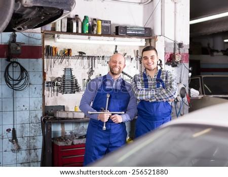 Portrait of two smiling professional car mechanics at garage - stock photo