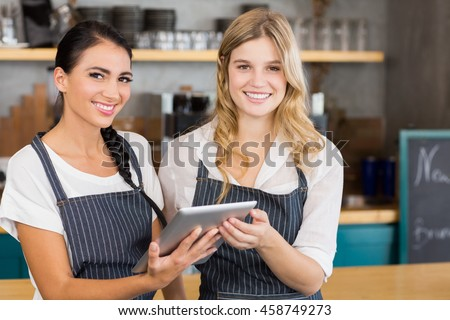 Portrait of two smiling waitresses using digital tablet at cafe