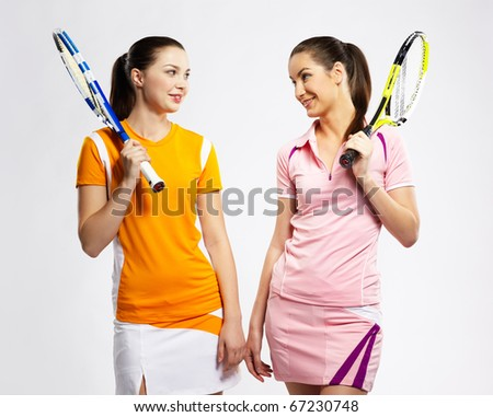 portrait of two sporty girls tennis players with rackets - stock photo