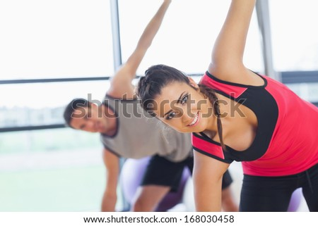 Portrait of two sporty people stretching hands at yoga class in fitness studio - stock photo