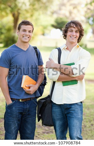 Portrait of two standing handsome students talking in a park - stock photo