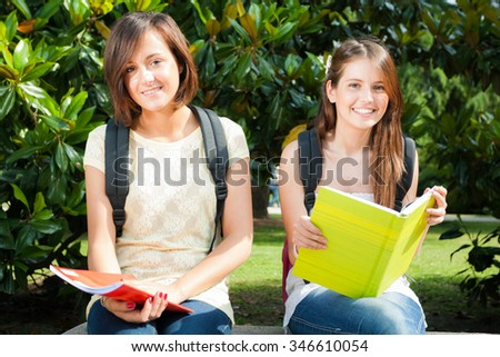 Portrait of two students in a park - stock photo