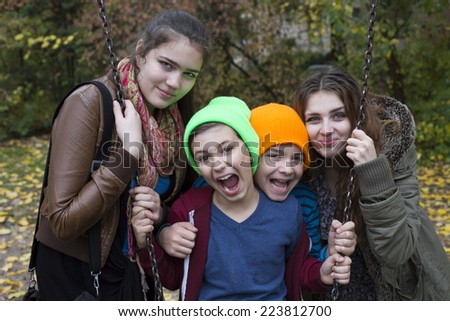 portrait of two teenage girls and two boys on a playground - stock photo
