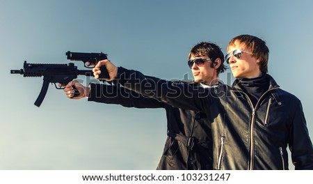 Portrait of two tough guys with guns