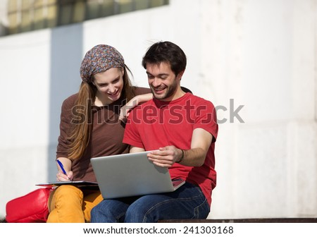 Portrait of two university students studying with laptop outdoors - stock photo