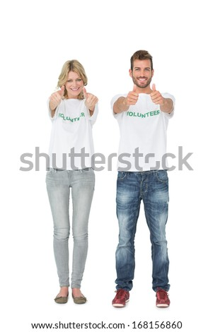 Portrait of two volunteers gesturing thumbs up over white background