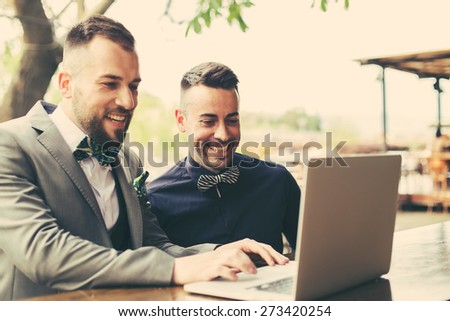Portrait of two web designers discussing a project in front of a laptop - stock photo