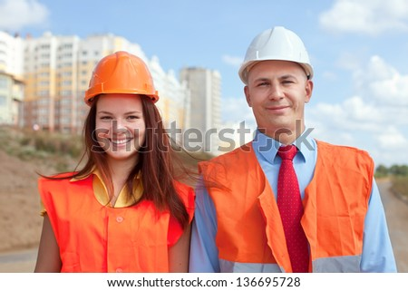 Portrait of two white-collar workers wearing protective helmet works on the building site - stock photo