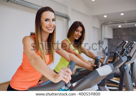 Portrait of two women doing cardio exercises at gym - stock photo