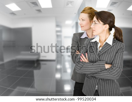 portrait of two women in office clothes on unrecognizable interior background - stock photo