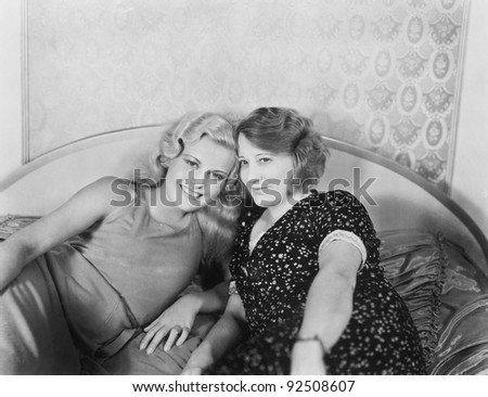 Portrait of two women lying on a bed - stock photo