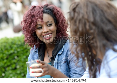 Portrait of two women taking a drink in a bar. Urban background. Multiethnic group - stock photo