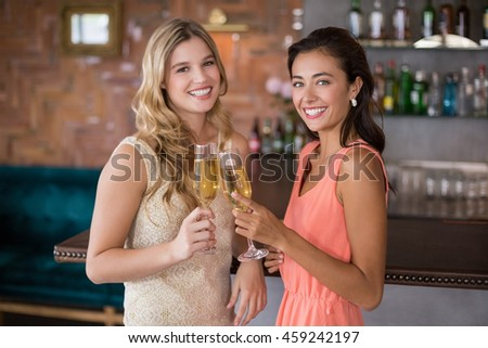 Portrait of two women toasting a glass of champagne in restaurant