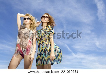 Portrait of two young adult sensuality and sexy beautiful blonde and brunette woman in multicolor dress and sunglasses on background blue sky - stock photo