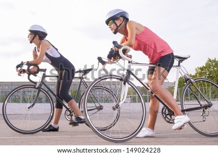 portrait of two young attractive females holding their race bikes and standing on a track. horizontal image
