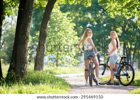 Portrait of two young beautiful cheerful women girlfriends wearing jeans shorts sitting on bikes on sidewalk in park on sunny summer day, looking back with smile - stock photo