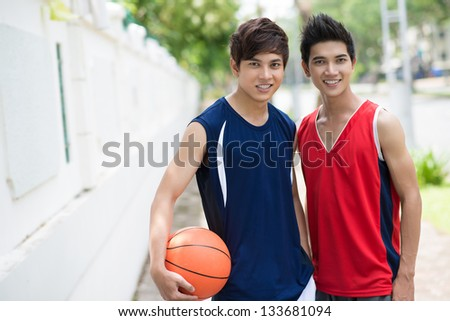 Portrait of two young boys with a ball looking at camera - stock photo