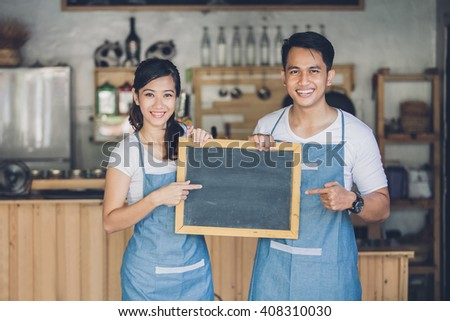 portrait of two young business partner open their coffee shop. standing with blank blackboard sign - stock photo