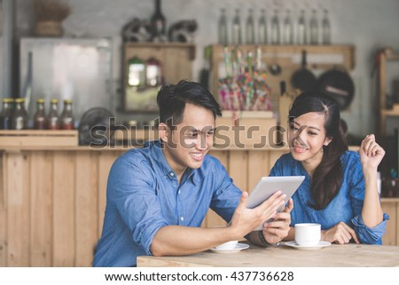 portrait of two young business partner using tablet together in the cafe
