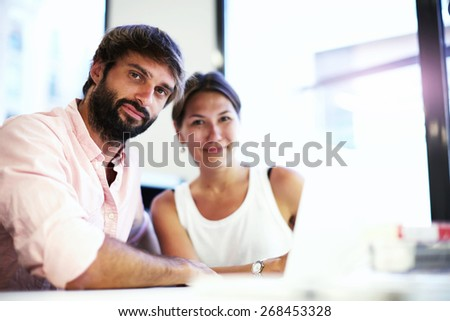 Portrait of two young business people at meeting, businesspeople having discussion working with computer indoors, young students learning at library, company partners talking about project - stock photo