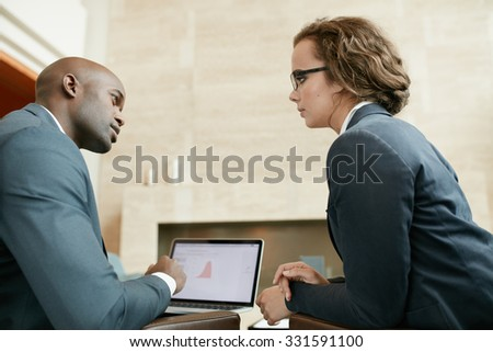 Portrait of two young business people in a cafe. Business partners in a serious business discussions at a restaurant. - stock photo