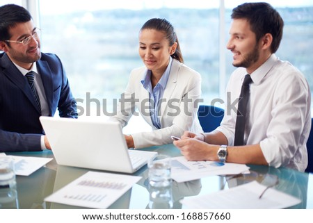 Portrait of two young businessmen looking at their colleague networking in office