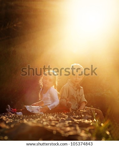 Portrait of two young children sitting together in the sunlight outdoors. brother and sister siblings