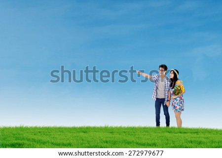 Portrait of two young couple walking together on the meadow under blue sky