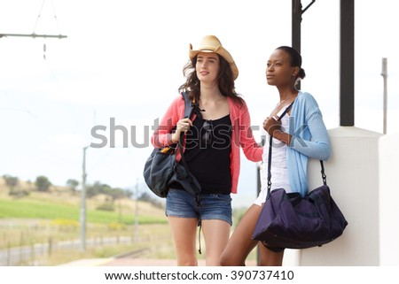Portrait of two young female friends waiting for train at railroad station  - stock photo