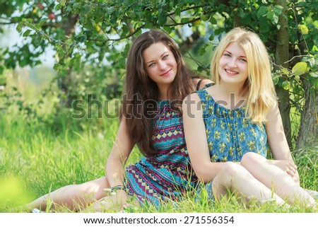 Portrait of two young friends are sitting and resting on green lawn grass in rural fruit-trees summer garden - stock photo