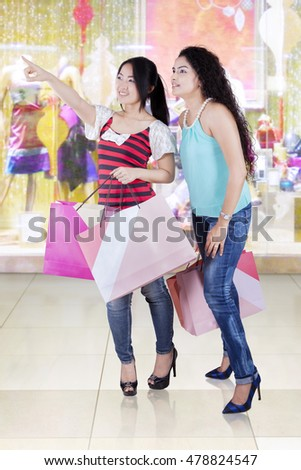 Portrait of two young girls shopping together and pointing at something in the mall
