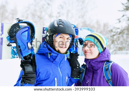 portrait of two young lovers with snowboard in the hands.Young couple in love with snowboarding suits outdoors in winter on the mountain.  Tender feelings with a smile and eyes.