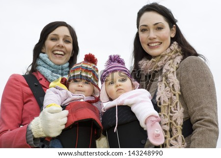 Portrait of two young mothers with their babies in winter clothing