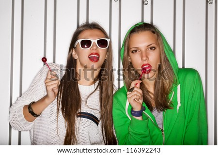 Portrait of two young naughty girls sucking lollipops, outdoors