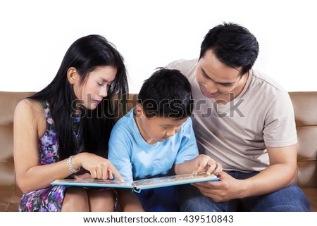 Portrait of two young parents and their son sitting on the couch while reading a story book together