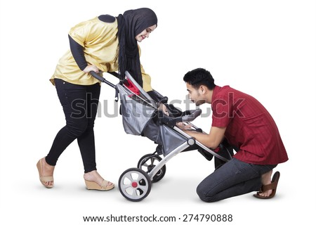 Portrait of two young parents take care their baby in the baby carriage, isolated on white background - stock photo