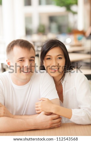 Portrait of two young people embracing, looking at camera and smiling - stock photo