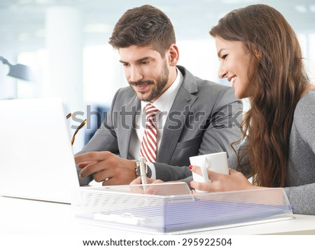 Portrait of two young professionals sitting in front of computer and consulting. Business people working together on next project.  - stock photo