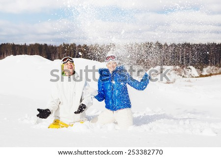 Portrait of two young snowboarders having fun sitting in snow on hill. Sunny winter day. Nature background. Outside - stock photo